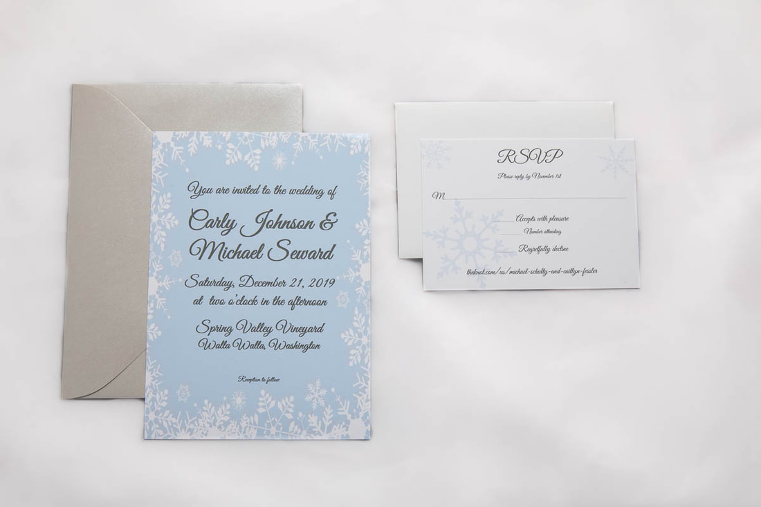 Snowflake wedding invitation with an ice blue background, matching RSVP, gray RSVP envelope, silver invitation envelope