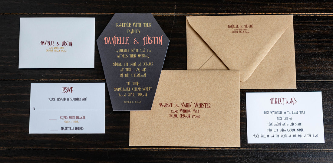 Black and maroon/dark red vampire inspired wedding invitation shaped like a coffin with RSVP and addressed envelope along with a guest addressed envelope with return addressing on the back flap.