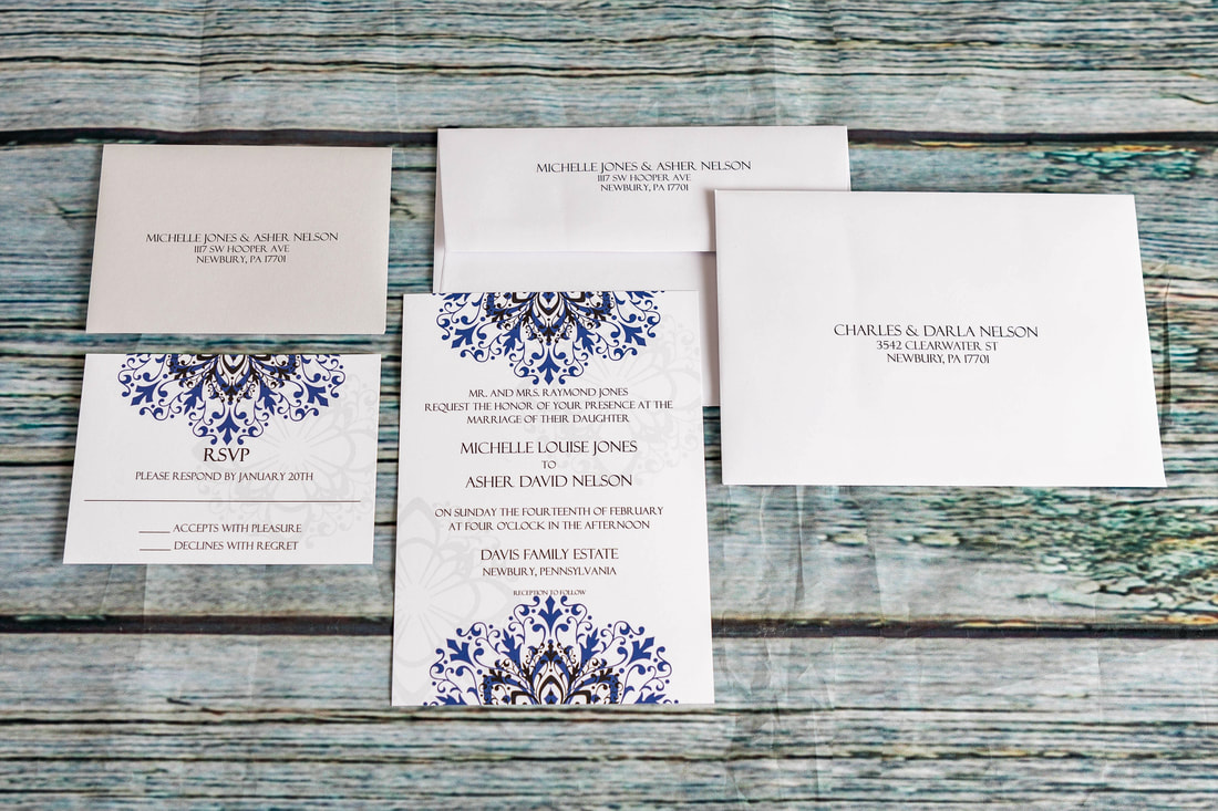 Purple, black and grey flourish design at the top and bottom of wedding invitation.  Rsvp card, rsvp envelope with address, guest address and return address on envelope.